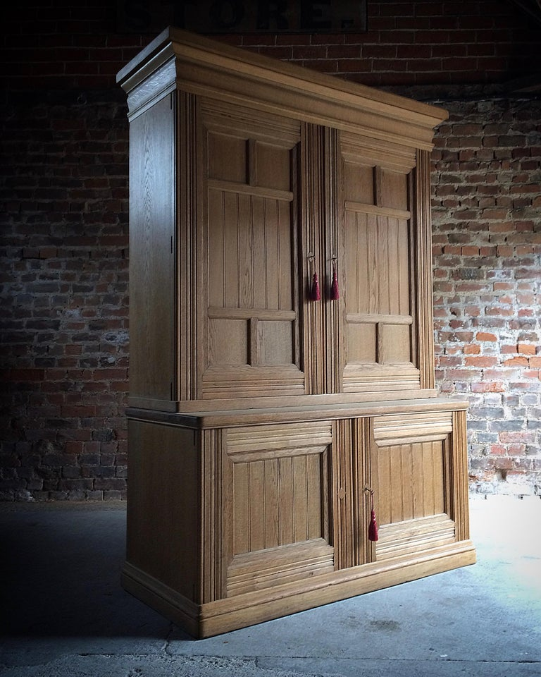 A large late 19th century ash Housekeepers cupboard circa 1890 the large overhanging cornice over a large pair of panelled doors, opening to reveal fitted interior with numerous shelves and four drawers, maker's mark and monogram to one door, over