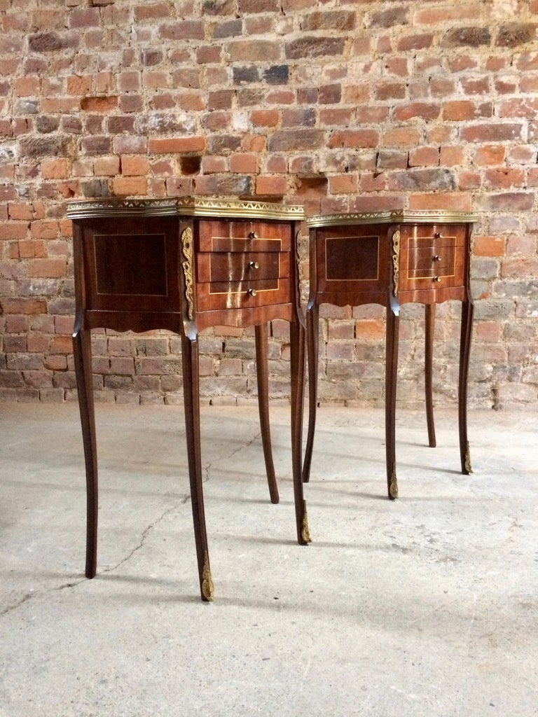 A wonderful pair of French rosewood and burr walnut bedside cabinets / nightstands or side tables dating from the mid-20th century, with applied brass galleried surrounds with inlaid tops over three short drawers with tall and elegant out swept legs