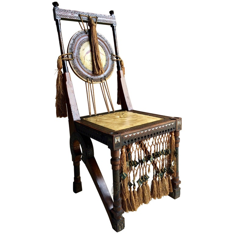 Carlo Bugatti (1856-1940) side chair made from walnut with embossed copper and pewter inlay, velum seat and back painted with stylized flora with original silk tassels, circa 1900.  Background:  Carlo Bugatti was an Italian furniture designer