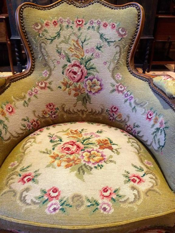 A beautiful antique French Mahogany salon armchair with stuff-over arms and seat with near matching footstool, upholstered in floral needlework 'Roses' with gold velvet back, scrolled arms, standing on elegant cabriole legs, the armchair is offered