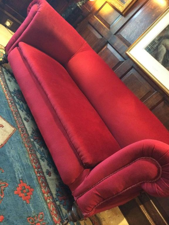 A beautiful antique Victorian Chesterfield three-seat sofa recently reupholstered in lush 'Scarlet Red' velvet material, the sofa has a lever to the right allowing the right arm to drop at adjustable heights, offered in excellent condition, sitting