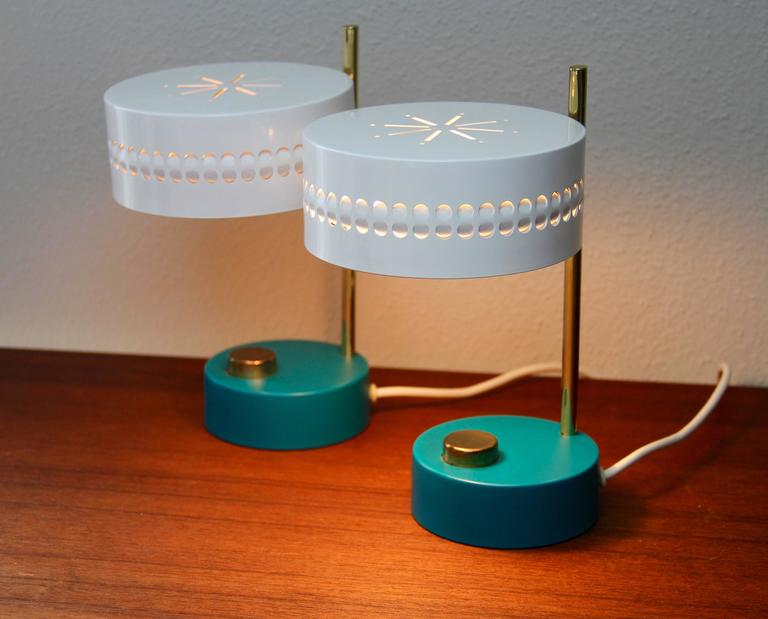An absolutely stunning and rare pair of table lamps by Mathieu Mategot circa 1950-1959 with oversized white perforated metal shades and teal colored bases - complimented by oversized brass switches. Simply perfect design - exactly what you expect