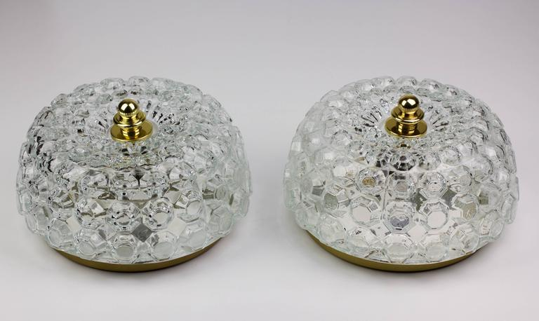 Elegant Mid-Century clear glass flush mount light fixtures by Helena Tynell for Glashütte Limburg, circa 1968. The honeycomb patterned design casts a stunning light through the crystal clear glass - whether wall or ceiling mounted the add a touch of