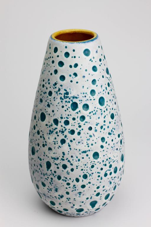 Beautiful Mid-Century example of West German pottery by Ü-Keramik, circa 1960. Featuring a stunning color combination of white over turquoise with a yellow inner glaze, the outer glaze resembles the surface of the moon with craters exposing the