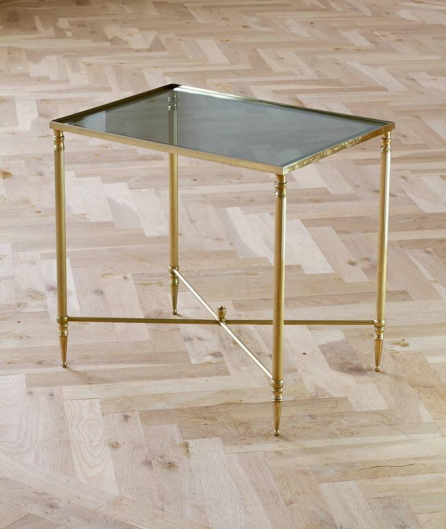 A wonderful tall side or end table attributed to Maison Jansen, circa 1970. Made from solid brass in the neoclassical style and featuring a dark toned smoked glass tabletop with a mirrored border. This delightful table, not dissimilar to designs by