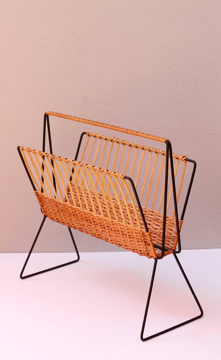 This large, oversized magazine stand or holder, attributed to Austrian Carl Auböck, circa 1950s, features woven wicker / rattan strands which wrap around the black painted steel wire frame creating, what is, a wonderfully minimal, modernist piece of