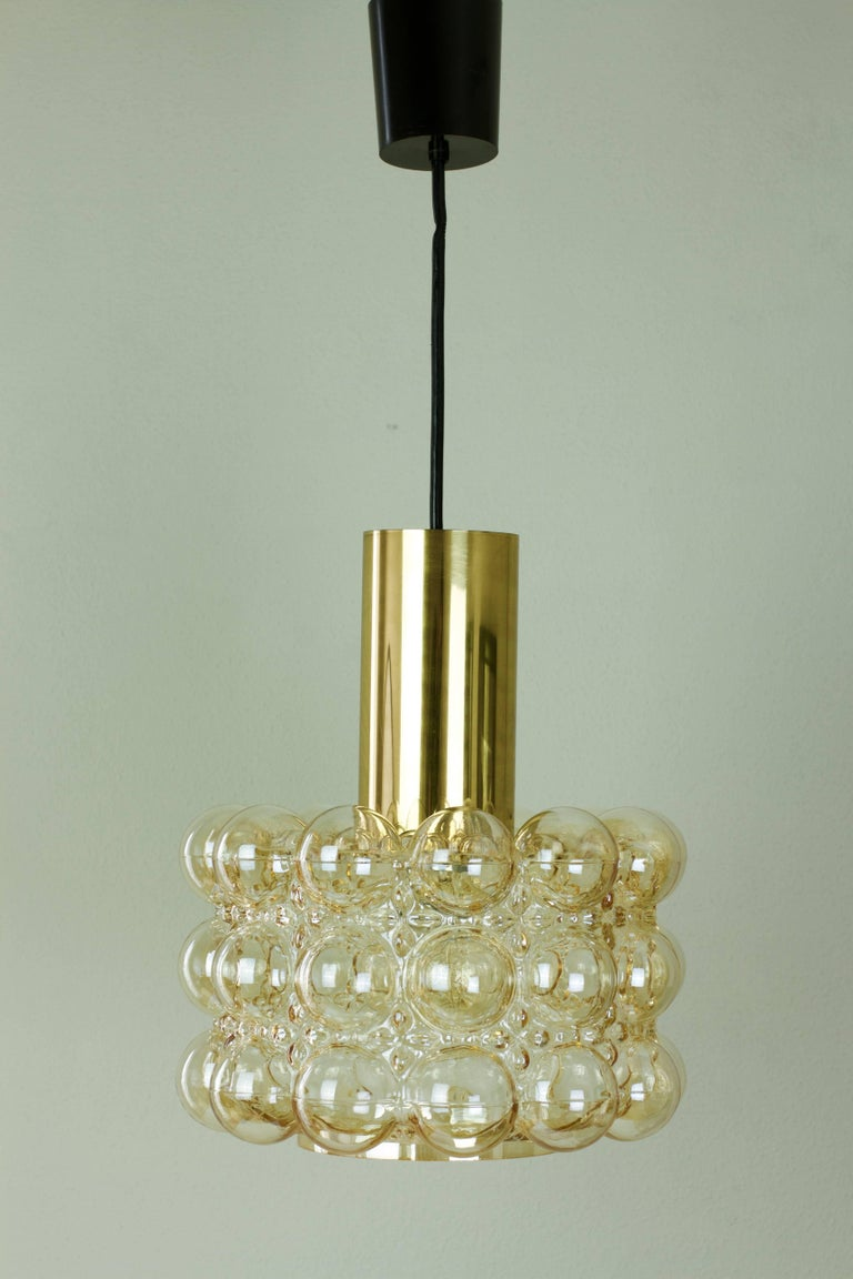 Late 1960s bubble glass ceiling pendent light designed by Helena Tynell for Glashütte Limburg. The light features a beautiful lampshade made from amber or champagne colored / coloured glass with a polished brass cylinder on top.