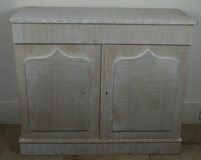 The ultimate in understated elegance.  The piece has been repainted in white on the original pine. It has been limed so the grain is clearly visible.  The only ornamentation is the shield shape panel to the doors.  2 cupboard doors surmounted by a