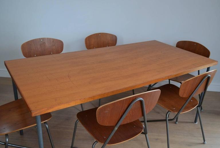 A 1970s vintage Industrial teak dining table and a set of six stacking chairs by Remploy.