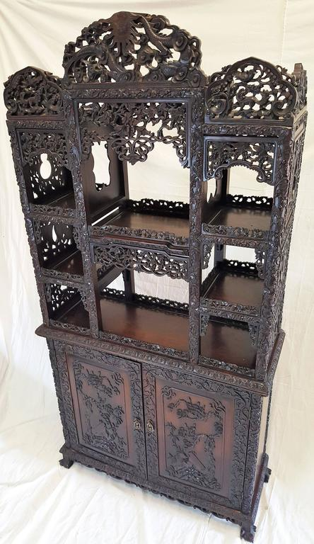 Expressing long life and happiness this beautifully highly reticulated Hong Mu curio cabinet is of the Qing dynasty. Birds, animals, berries, vines and the never ending coil are beautifully carved into this dark hong mu or rosewood cabinet.
