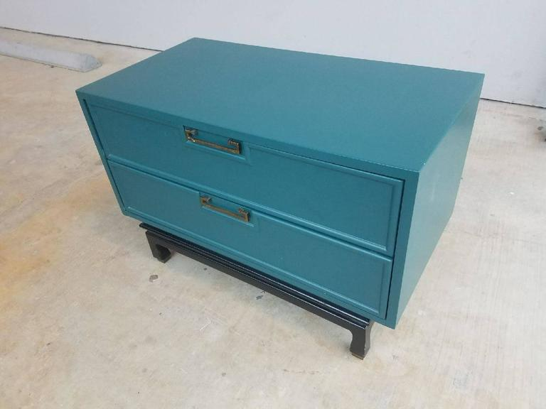 Lovely pair Mid-Century Modern two-drawer nightstands lacquered in peacock blue over walnut, showcase the clean lines attributed to American of Martinsville quality furniture designs. Sometimes labelled as Danish Modern this piece with an Asian