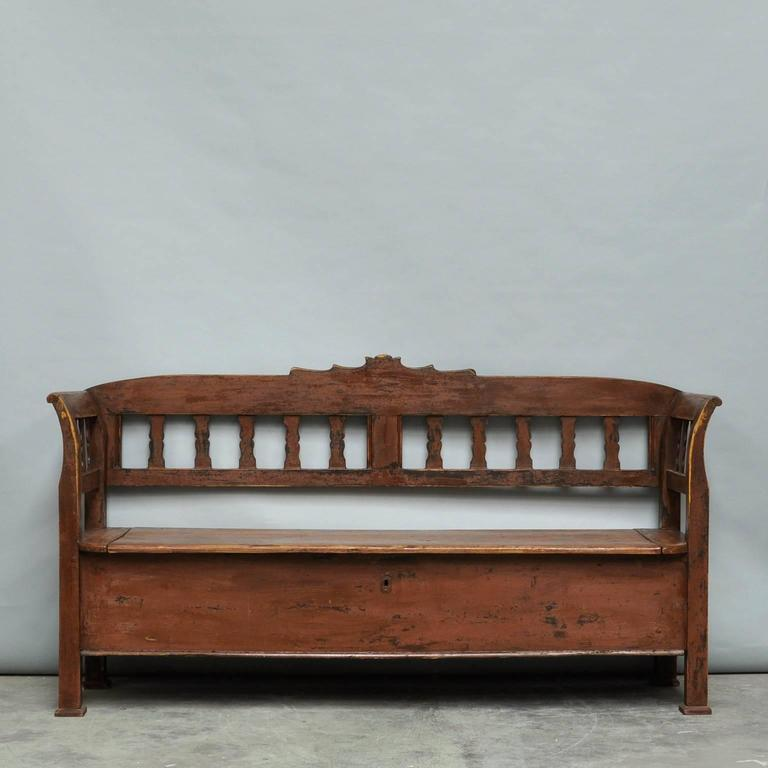 This pine storage bench from Hungary was produced circa 1920 and retains its original paint. The seat opens upwards to reveal a three compartment storage space. The distressed painted finish where the paint is worn away allows the natural pine to