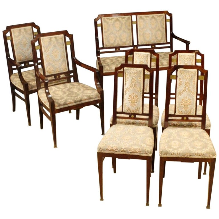 Pair of Art Deco French armchairs from the first half of the 20th century. Furniture carved in mahogany wood with golden wood decorations on the back, brass feet and small bronze decoration. Pleasant upholstered armchairs in velvet of beautiful