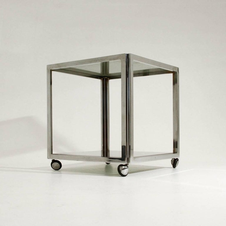 Nice table from the 1970s. Square chromed metal structure, two glass shelves smoked, wheels to be moved. Good general conditions.  Dimensions: Width 40 cm, depth 40 cm, height 42.5 cm.