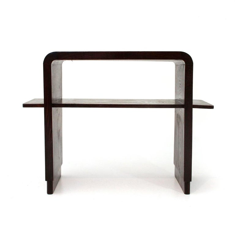 Console of Italian manufacture produced in the 1940s. Veneered and stained wood frame. Top with rounded corners. Central shelf and two small side shelves. Foot with lower section. Structure in good condition, some signs due to normal use over