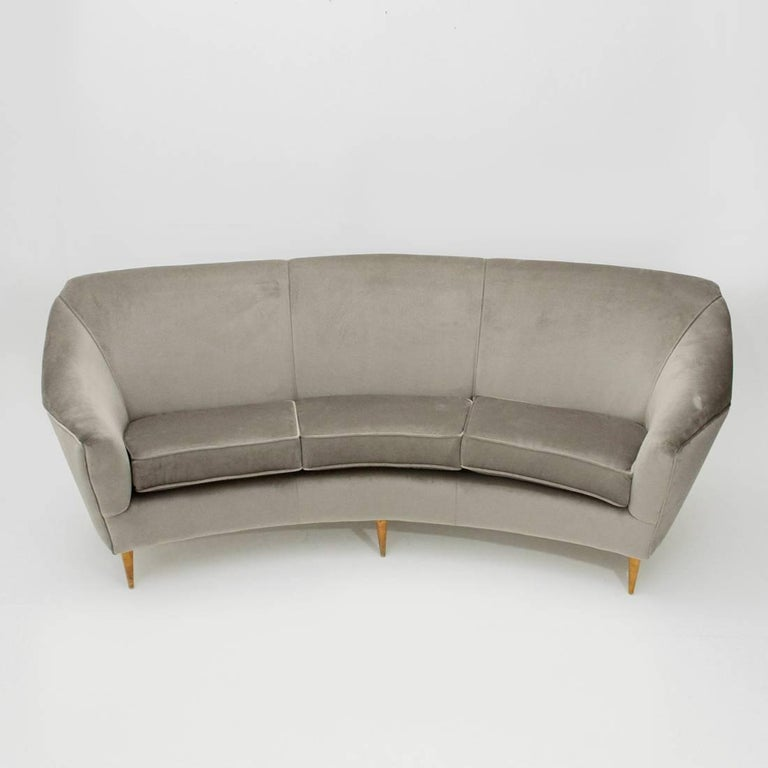 Italian sofa produced in the 1950s. Wooden structure padded and lined with new velvet fabric. Sitting with upholstered cushions. Feet in wooden conical shape. Excellent general conditions.  Dimensions: Width 230, depth 92 cm, height 97 cm,