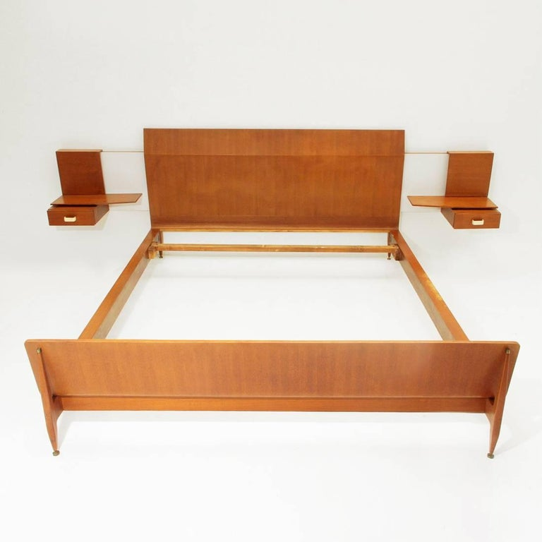 Bed produced in the 1950s by Galleria Mobili d'Arte from Cantù, company that also produced various Gio Ponti furniture. Teak veneered wood structure. Strong tapered legs and adjustable height feet in brass Headboard and bedside tables connected