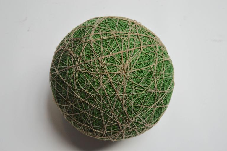 Huge vintage ball, made of discontinued yarn. The entire piece is made of string. Great colors with green centre and tan overlay. Unique decorative object and sculpture. Very heavy and solid, can be used as a stool.