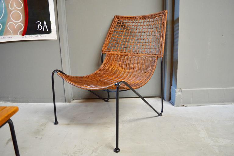 Fantastic pair of sculptural iron and wicker chairs. Woven wicker seat with braided back. Iron frame has a very unique design. Excellent vintage condition. Very rare set.