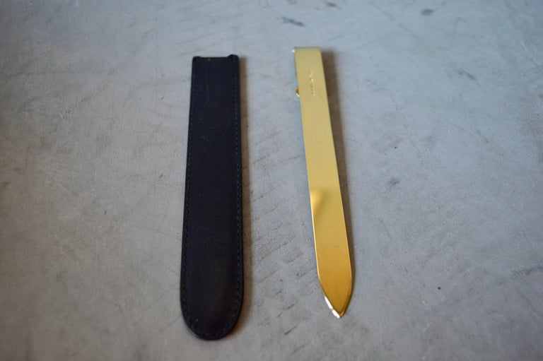 Sleek brass Gucci letter opener with leather case. Double G logo on brass. Marked Gucci on leather case. Good condition. Great desktop piece.
