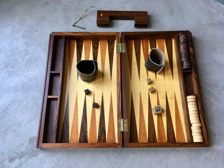 Stunning rosewood portable backgammon board. Handle slides out with inset brass pin. Board includes all pips, dice, leather cup holders and doubling cube. Gorgeous piece. Excellent condition.