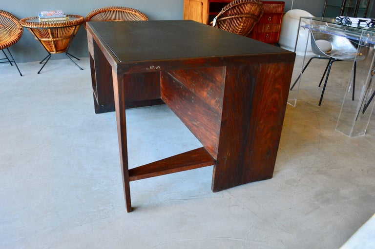 Stunning desk in Rosewood by Pierre Jeanneret. Made for the Chandigarh project. Angular leg and bookcase back. One of the most iconic pieces of modern design. Black leather top. Desk in excellent vintage condition.   Jeanneret Library chair