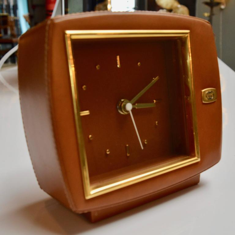 Gorgeous leather and brass table clock by Gucci. Great age and color to leather. Brass in excellent condition. Clock is in great working order. Double G brass logo on front. Gucci Italy label on bottom. Excellent condition overall.