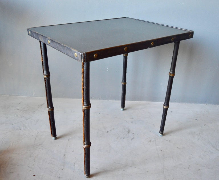 Stunning side table by Jacques Adnet. Entirely wrapped in black leather with black laminate top. This is a completely original, untouched, unrestored piece of Adnet furniture. Signature contrast stitching. Excellent vintage condition.