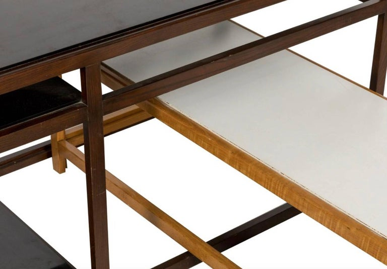 Fantastic pair of nesting console tables by Dunbar. Both consoles can stand alone or be nestled into each other. Great modular set. Rare two tone wood color. Very modern with clean lines. Dunbar tag underneath each piece. Sold as a pair. Excellent