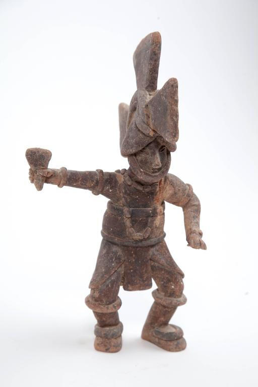 Incredibly charming antique Mexican clay warrior figure. From Nayarit, Mexico, circa 1900.  The piece has been professionally repaired at the neck, and has some losses to the necklace, and part of a hand.