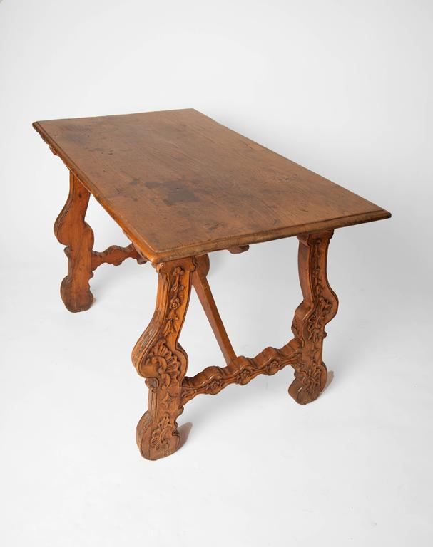 19th century Spanish walnut table with carved floral detailed legs.