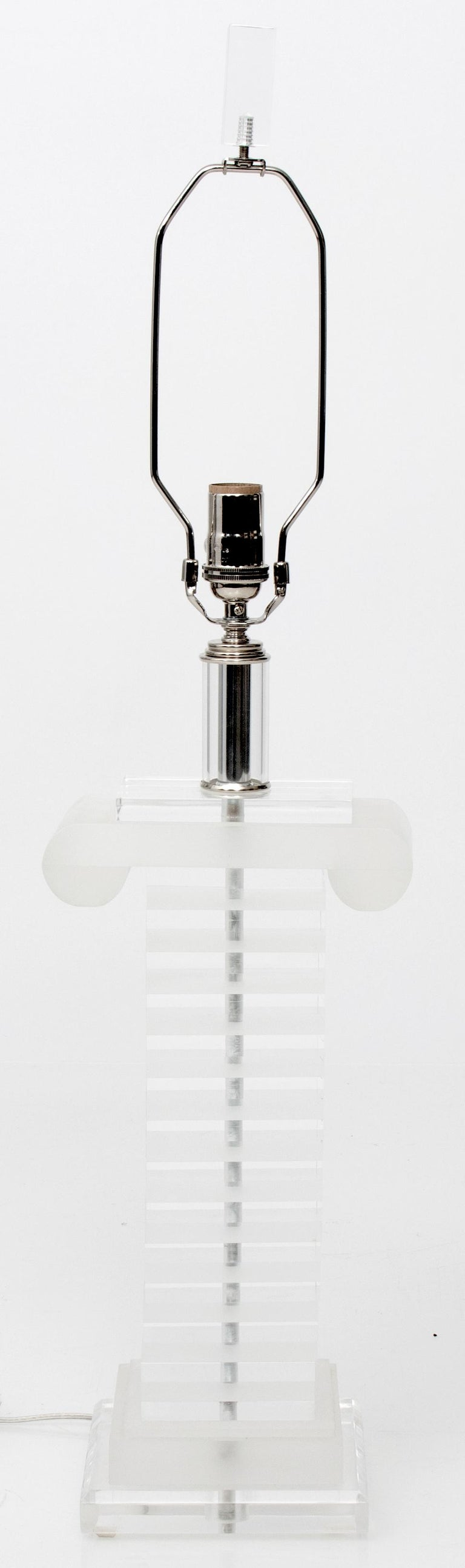Pair of Lucite column table lamps. Newly rewired. Off-white silk shades are included. Lamps are 31.5