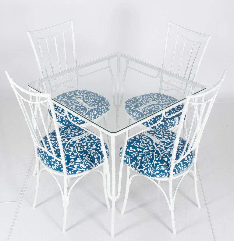 White metal faux bamboo dining set. Suitable for indoor or outdoor use. Square table with new clear glass top. Chairs and table are newly powder-coated in gloss white finish. Chairs are newly upholstered in Clarence House 'Fauve' outdoor fabric in