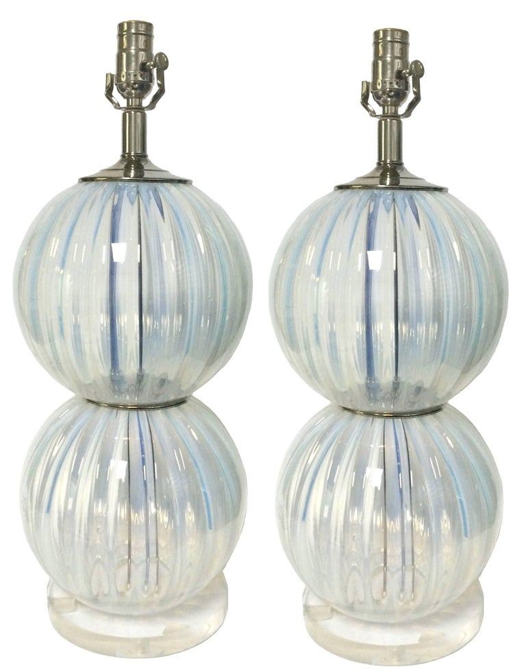 Pair of midcentury Italian Murano glass lamps. Ribbed opalescent glass with subtle blue undertones. Lucite bases. Newly rewired. Each lamp takes one standard bulb (not included). Lampshades not included.