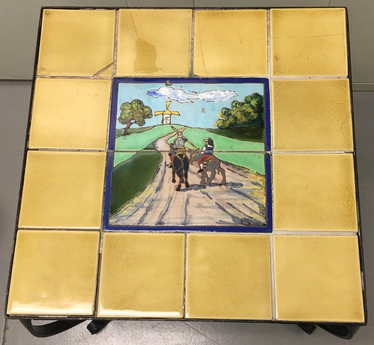 1930s Spanish tile-top wrought iron side table. Ceramic tiles depicting Don Quixote and the Windmill. Black wrought iron table base.