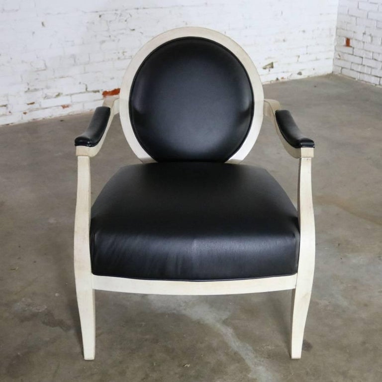 Handsome recently vintage fauteuil or open-arm side chair done in an antique white painted frame with black faux leather upholstery and transitional to contemporary styling. It is in fabulous condition and ready to use as a wonderful accent in your