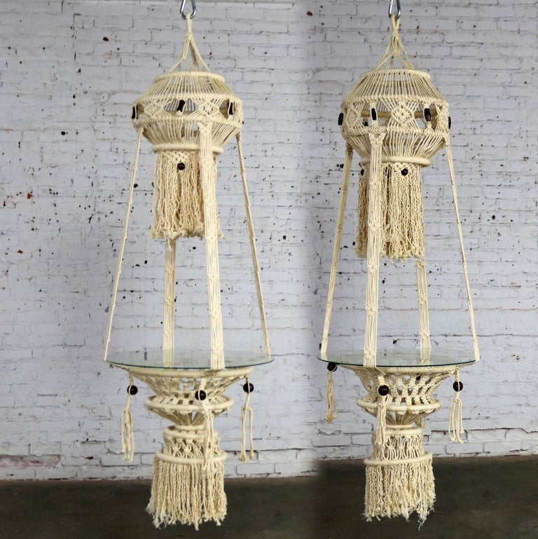 Beautiful pair of white cord macramé hanging tables with round glass tops. They are in wonderful age appropriate condition but not without minor flaws which do not take away from their overall look. Please examine photos, circa 1960s-1970s.