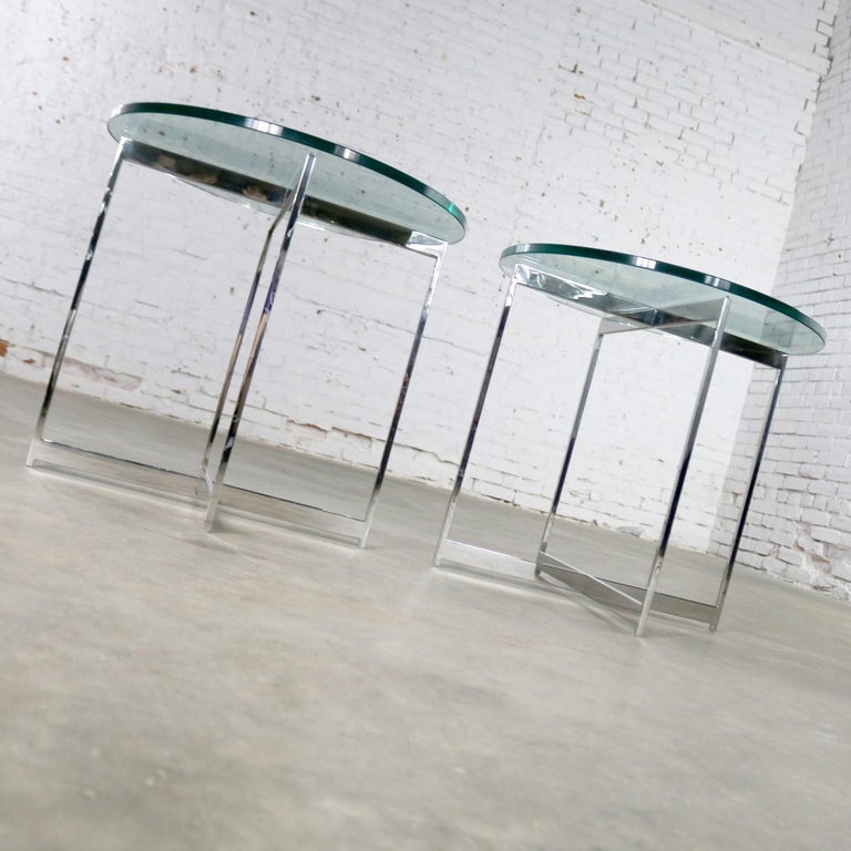 Exceptional pair of side tables with a chrome X-base and round glass tops after Mies van der Rohe and in the style of Milo Baughman as well. They are in fabulous vintage condition with only minor signs of age. Please see photos, circa