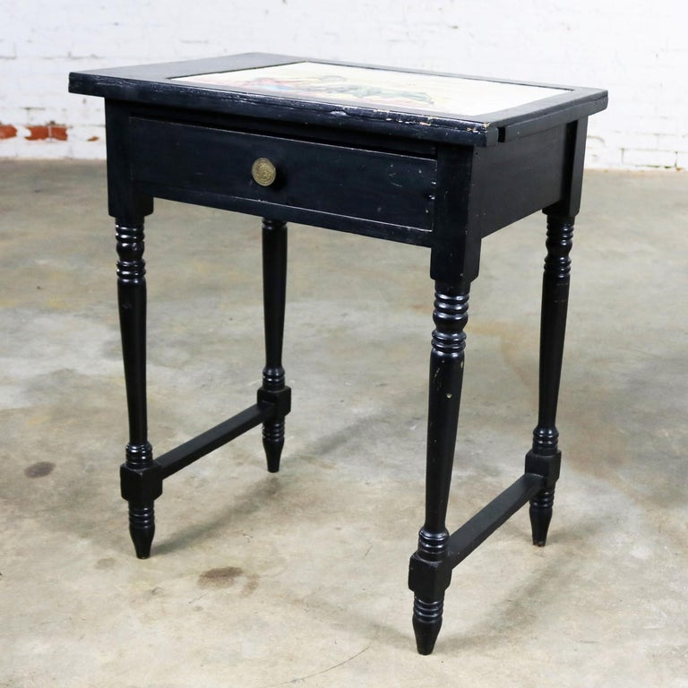 Awesome and unusual vintage end table, side table, or bedside table. Undoubtedly made in Mexico. It has a black painted finish, turned legs, a drawer, and an eight-piece signed tile insert in the top depicting a bullfight with both matador and bull.