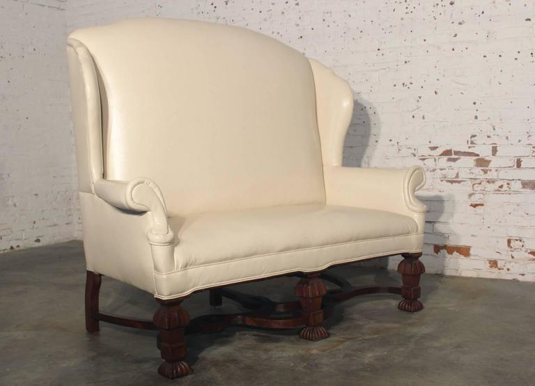 This high-style, high-backed settee features a dramatically high back and solid ornate feet. Its presence in a room, lobby, or lounge will not be missed. White faux leather upholstery in excellent condition. Minor wear in feet due to age.  Get a