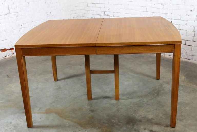 This vintage Mid-Century Modern dining table is so handsome with its bowed ends and beautiful mahogany veneer plus it is in very good age appropriate condition. The maker is undetermined but its great quality and good lines are not.