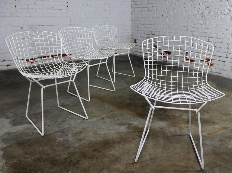 Classic Mid-Century Modern white wire Bertoia side chairs with purple seat cushions, 16 total. Buy one or all. Priced per chair. They are all in good over-all vintage condition. There is some minor chipping and rust spots to the Rilsan coating as