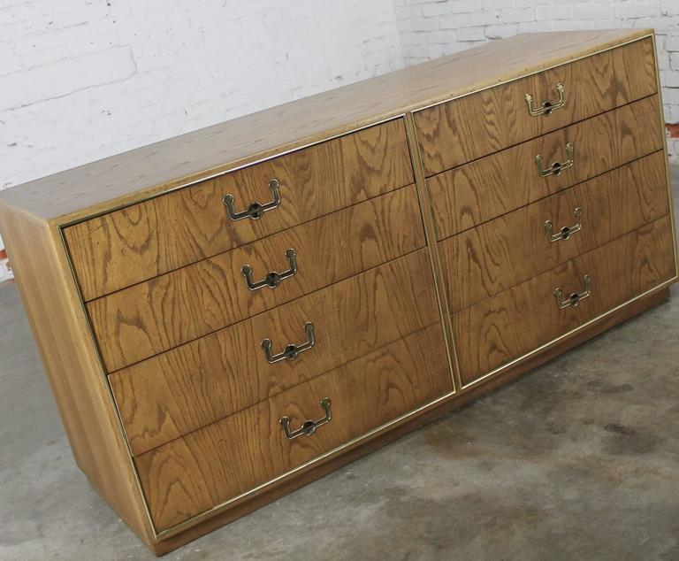 Elegant long and low Mid-Century campaign style eight-drawer dresser by Founders Furniture done in oak with antique brass colored hardware. This piece is in wonderful vintage condition circa 1974.
