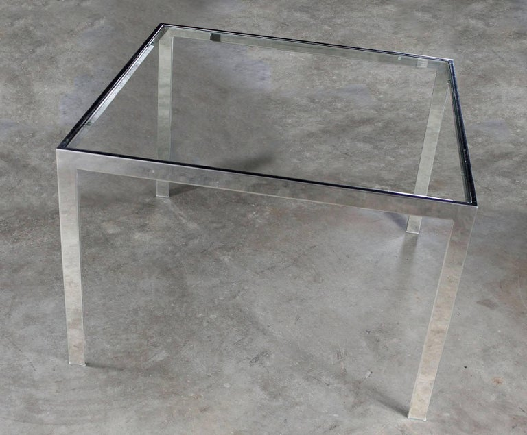 Handsome chrome and glass Parsons style end table attributed to Milo Baughman, circa 1970. In wonderful vintage condition with no outstanding flaws we have been able to detect. UPDATE: We have noticed there are small chips in the edges of the glass