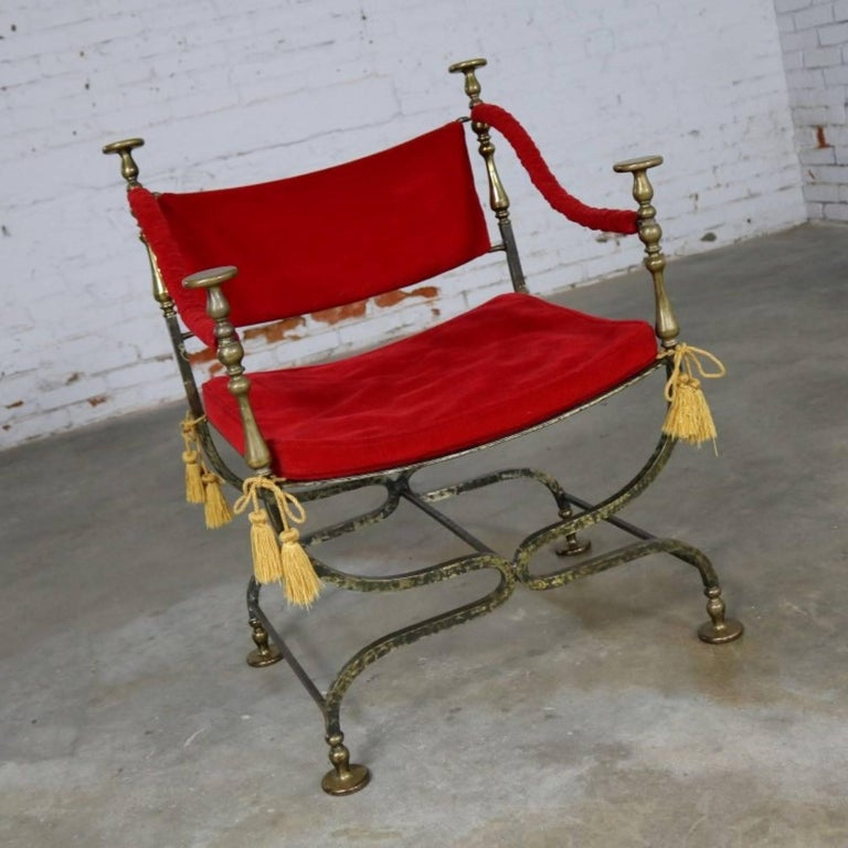 Stately and wonderful curule or Savonarola chair comprised of wrought iron and cast brass with red velvet. This chair frame is in perfect and beautiful condition and the velvet fabric is in good vintage condition and could be used; but, the foam in