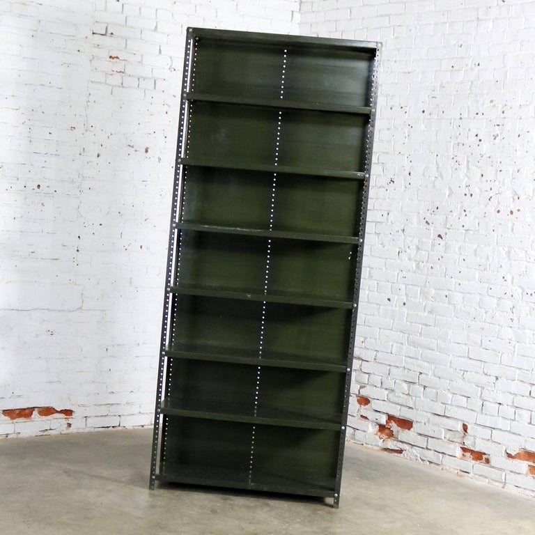 Wonderful Industrial steel bookcase or shelving unit. It retains its original Army green paint but with awesome age patina. It is in solid sturdy condition but has age and use dings, dents, scratches, and bare spots that creates a fabulous age