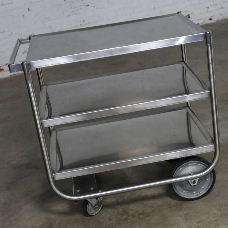 Awesome vintage Industrial three tier heavy gauge stainless steel rolling cart. It is in wonderful vintage condition with a nice overall patina to the stainless which includes small scratches and dings. The wheels are galvanized with hard rubber