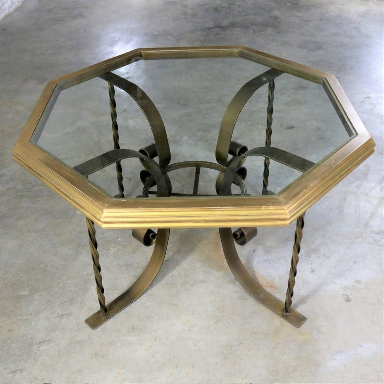 Handsome wrought iron Hollywood Regency style dining table with a wonderful octagon shaped wood rimmed glass top. It is in fabulous condition. The iron base has its original gold painted finish, which with age and use has gained a marvelous patina