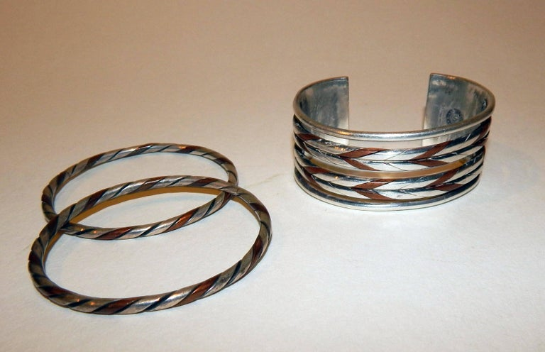William Spratling, Taxco, Mexico, circa 1940s bracelet set  Early copper and sterling cuff marked Spratling, made in Mexico and sterling, circa 1940. The set includes 2 unmarked bangles by Spratling in the same style. The cuff measures 1 1/8