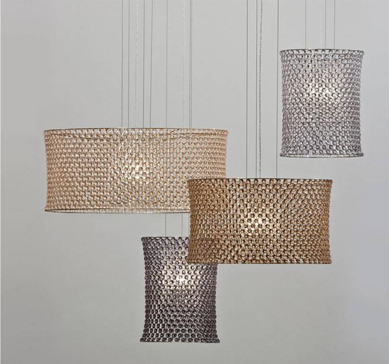 Elegant and modern, the Aires pendant lights are made of two seamless circular structures held by a net sewn of crystal gems of regular geometrical shape. The concave profile reveals the bejeweled mesh. Perfect as a large centerpiece or for small